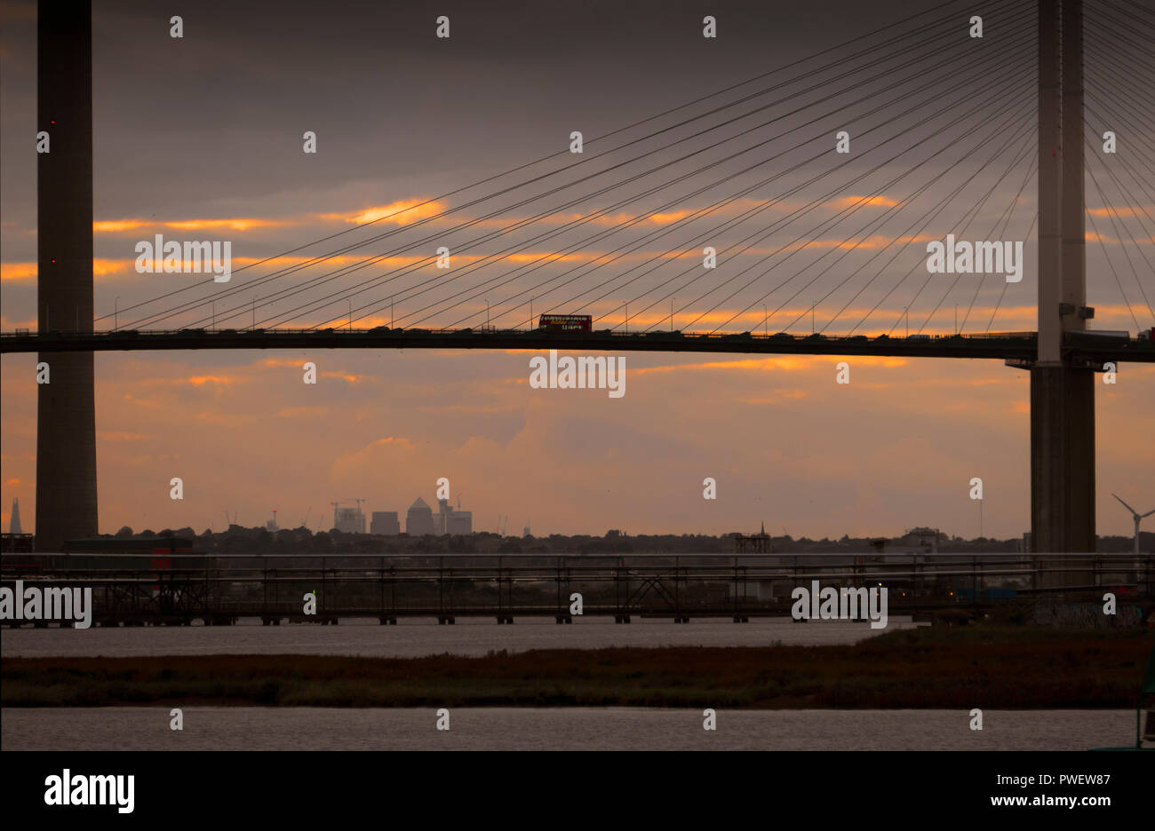 A London bus crosses the River Thames over the Dartford Crossing or Queen Elizabeth Bridge between Essex and Kent, England. - Stock Image