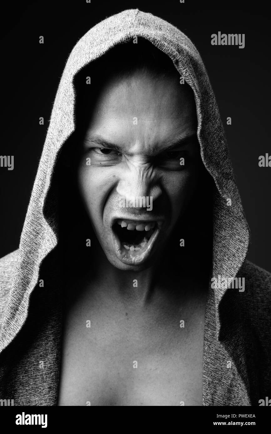 Rebellious man against black background in black and white - Stock Image