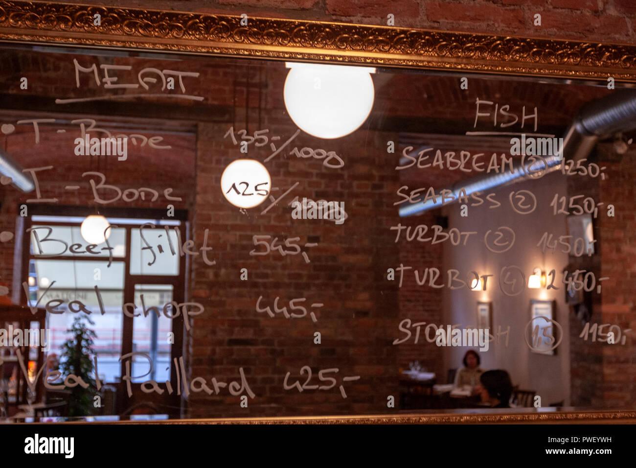 Today's menu written in a mirror in a restaurant in Prague, Czech Republic. - Stock Image