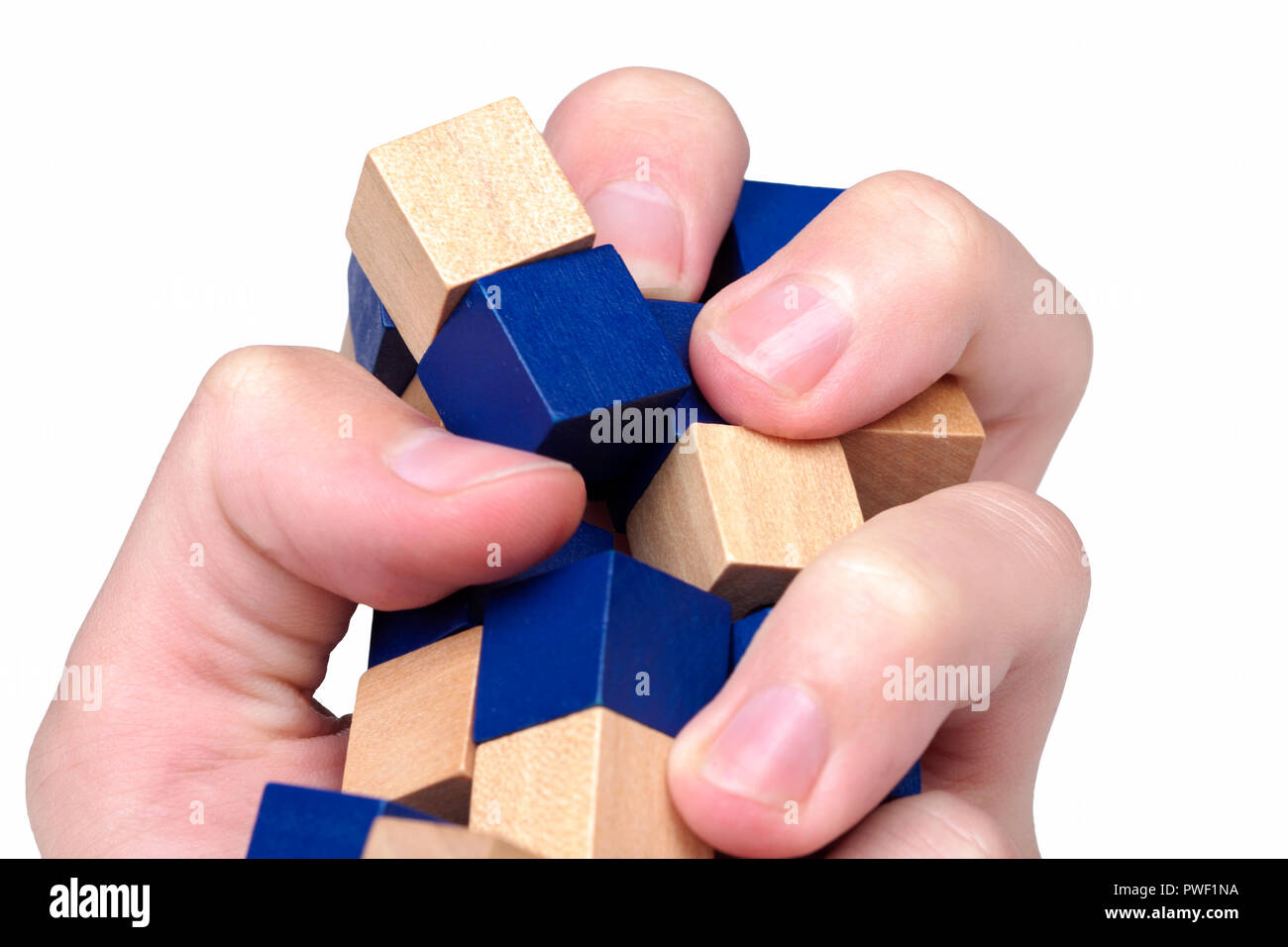 Hand violently squeezing, crushing and knocking down a structure made of wooden blocks - Stock Image