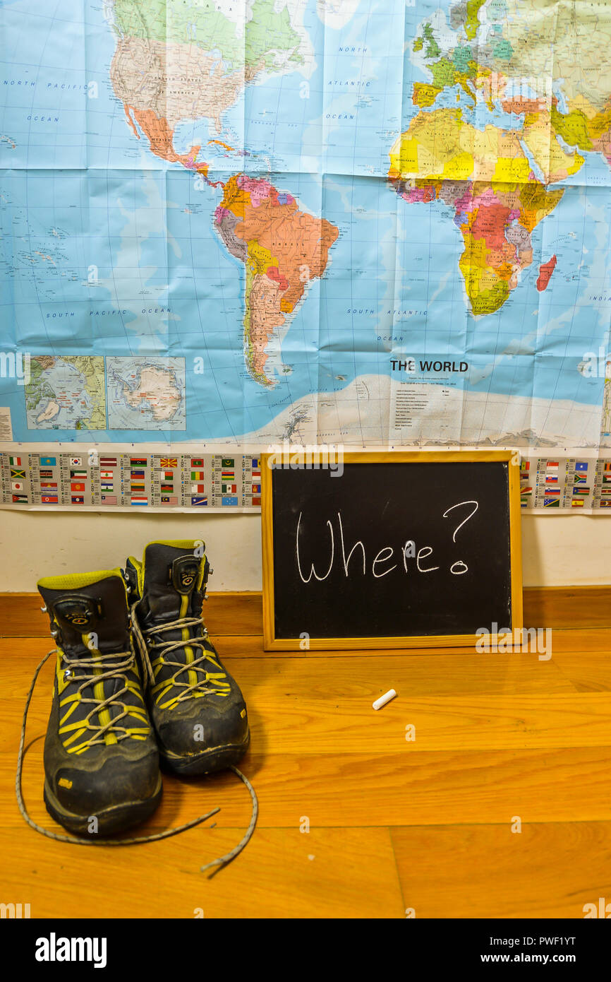 A chalk board with where written on and a world map - Stock Image