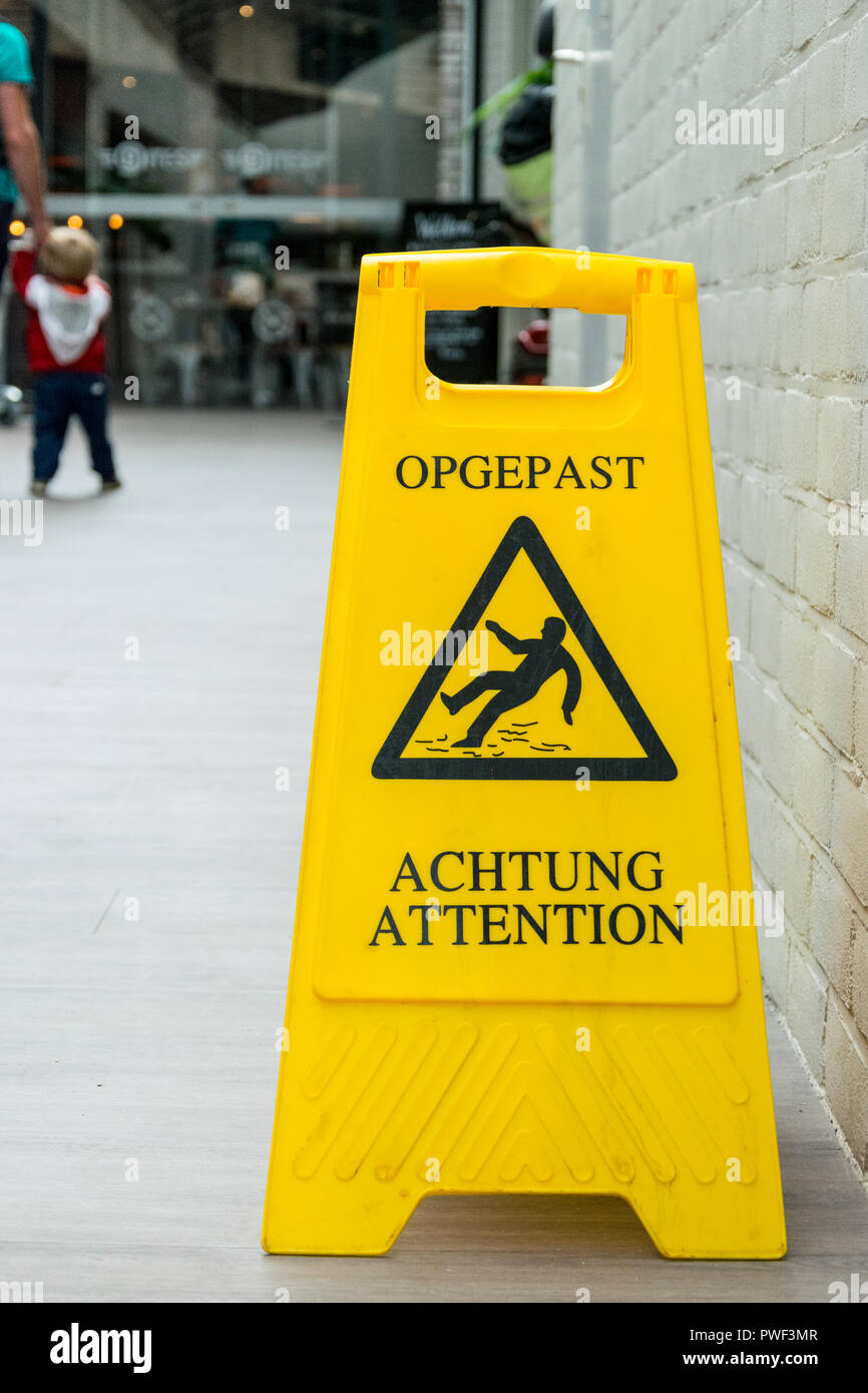 Warning yellow plastic floor sign Opgepast/Achtung/Atetntion, slippery wet floor - Stock Image