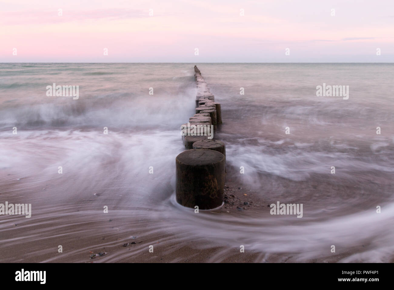 At a stage on the Baltic Sea flows picturesquely the water, long exposure. - Stock Image