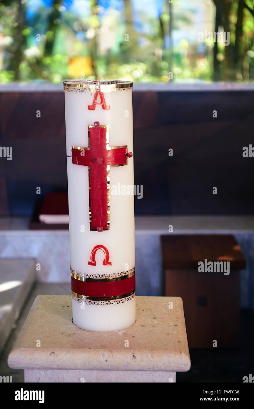 Paschal candle at catholic church, showing the cross in red and golden, and the Greek letters Alpha and Omega Stock Photo