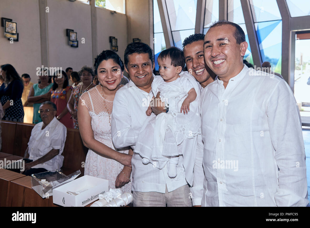 MERIDA, YUC/MEXICO - NOV 18, 2018: Godfather and wife hold their goddaughter, dressed in christening robe. Father and his brother next to her. - Stock Image