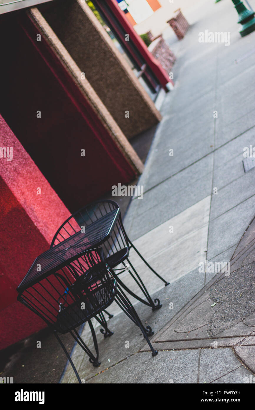 Abstract table and chairs on a city sidewalk with muted tones - Stock Image