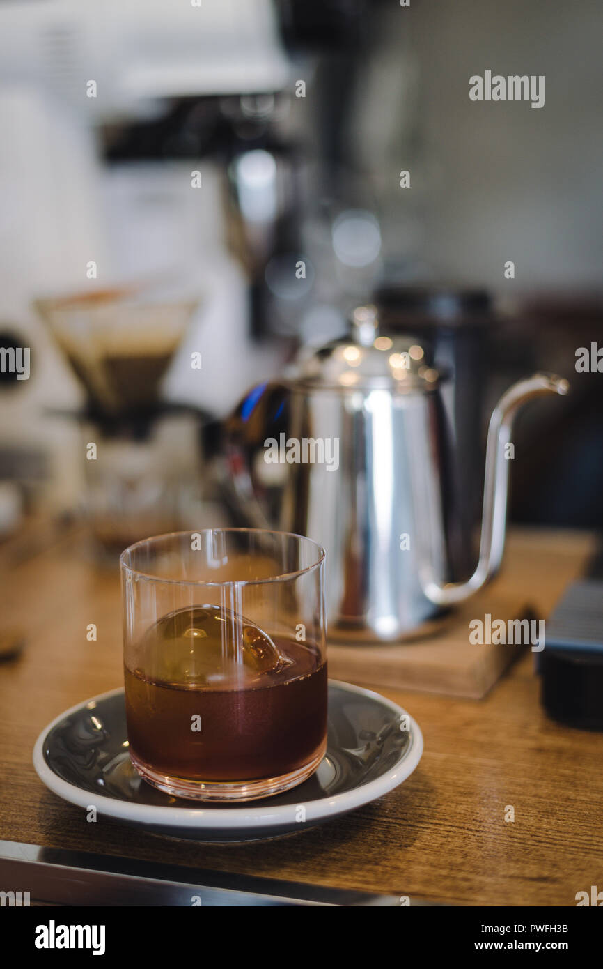Iced drip coffee with ice ball in glass with blur coffee bar scene - Stock Image