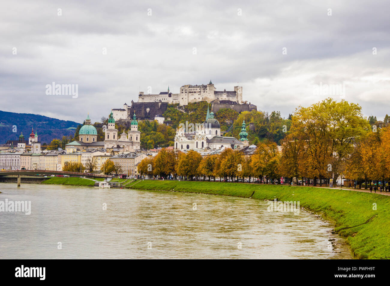 Famous classic view of historic old  city of Salzburg  with Festung Hohensalzburg. View of Salzburg over Salzach river on a cloudy autumn day. - Stock Image