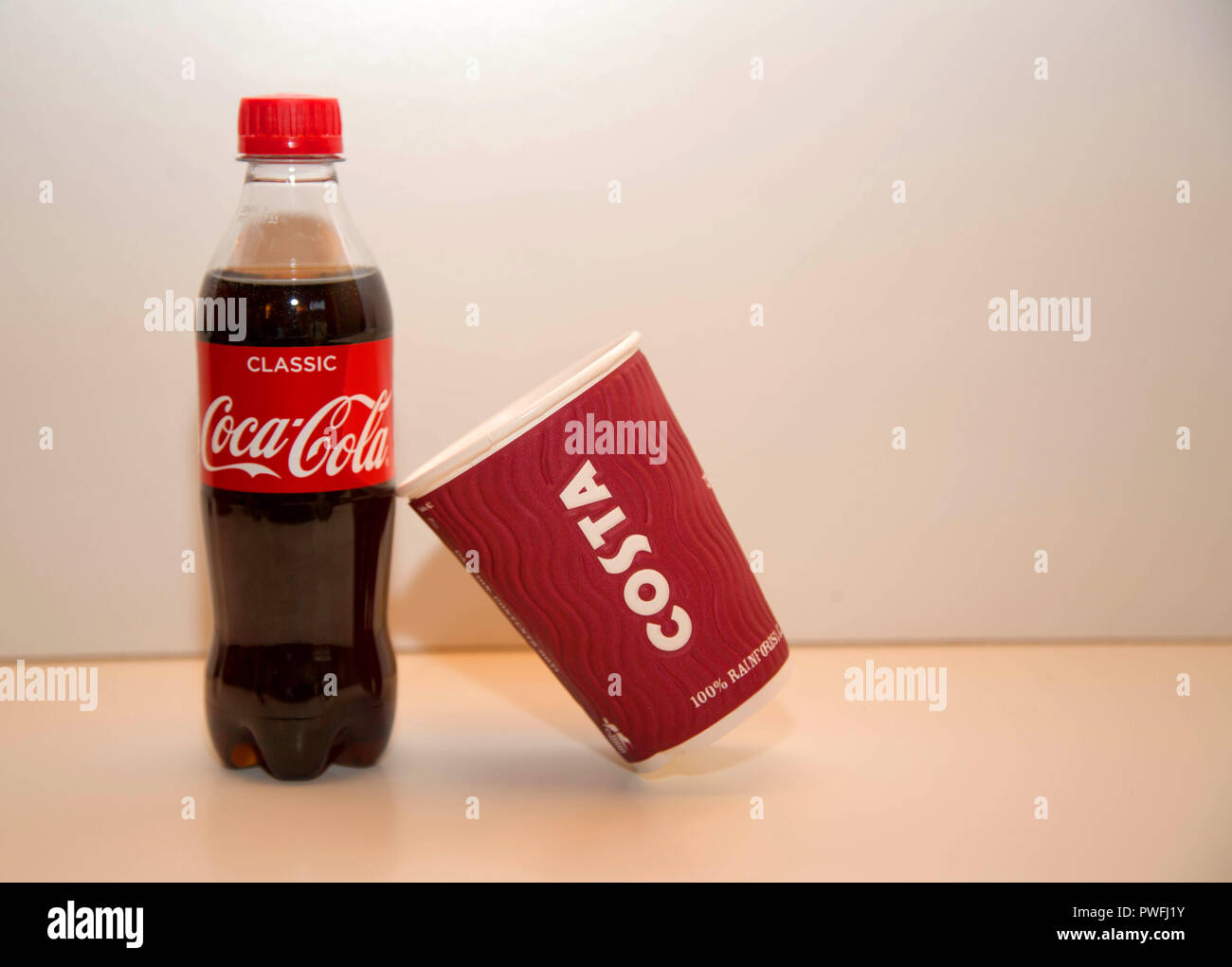 Coca-cola and Costa cup on plain background - Stock Image