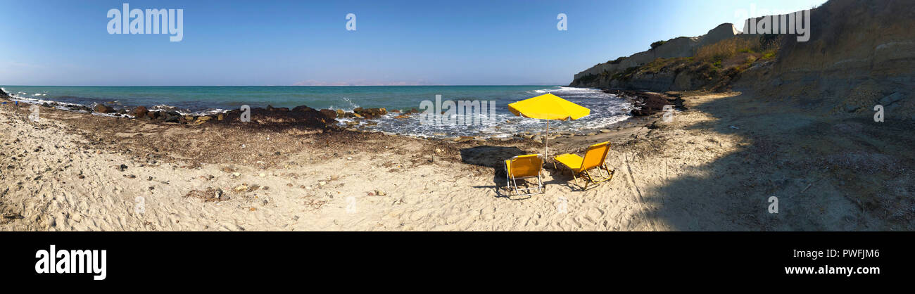 Panorama of two yellow lounge beach chairs and a parasol on the beach of a tropical island in front of the sea. Graphic ressource for web design. Stock Photo