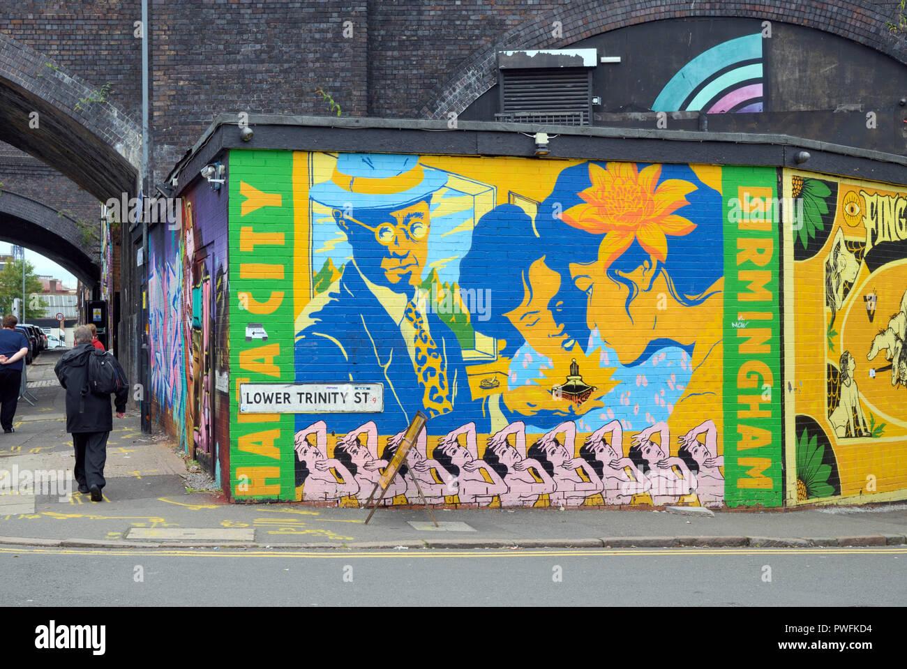 Pedestrian Walks Past Street Art in the Run-down Inner City Streets of Digbeth Birmingham England - Stock Image