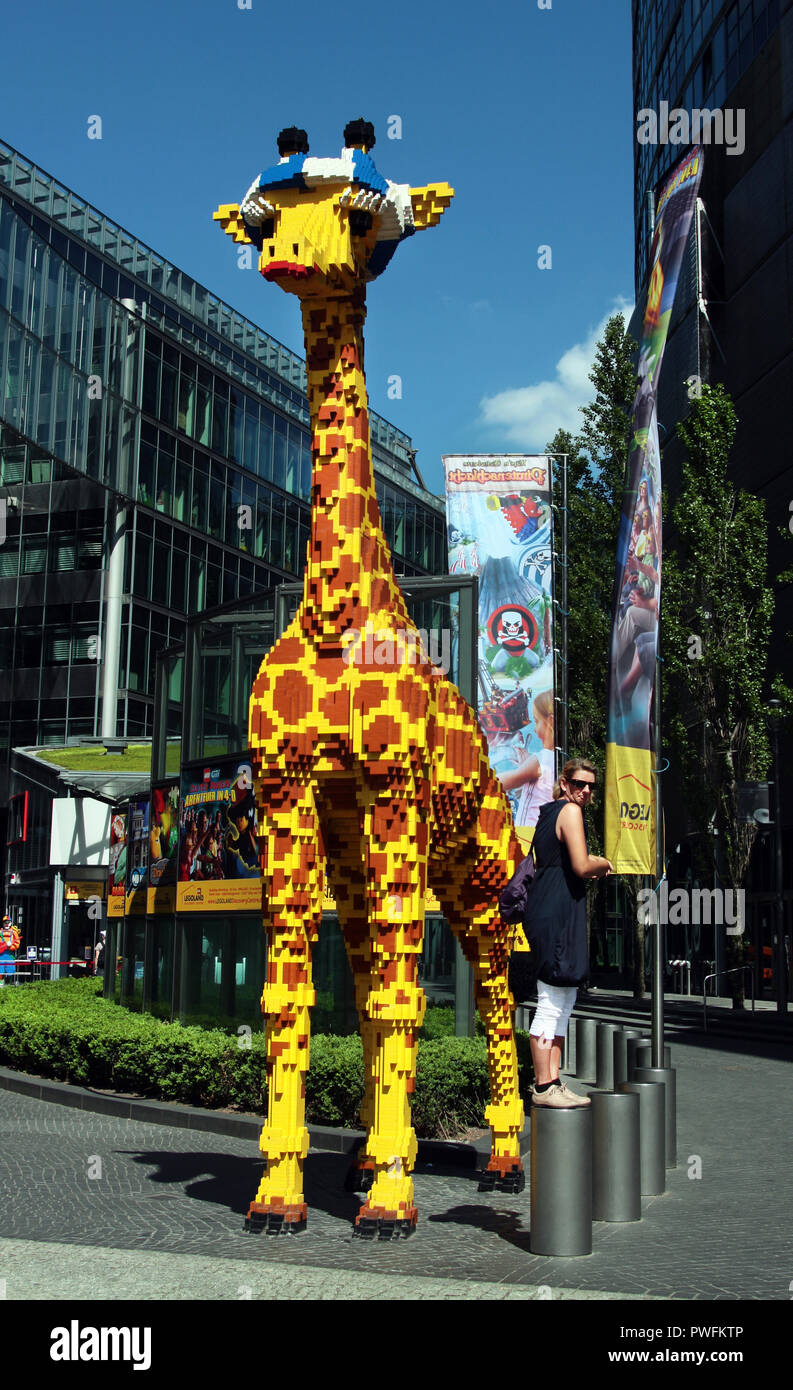 A life size representation of a giraffe mad from LEGO bricks stands in the Sony Centre in Potsdamer Platz, Berlin. It is, of course, the representation of a baby giraffe. - Stock Image