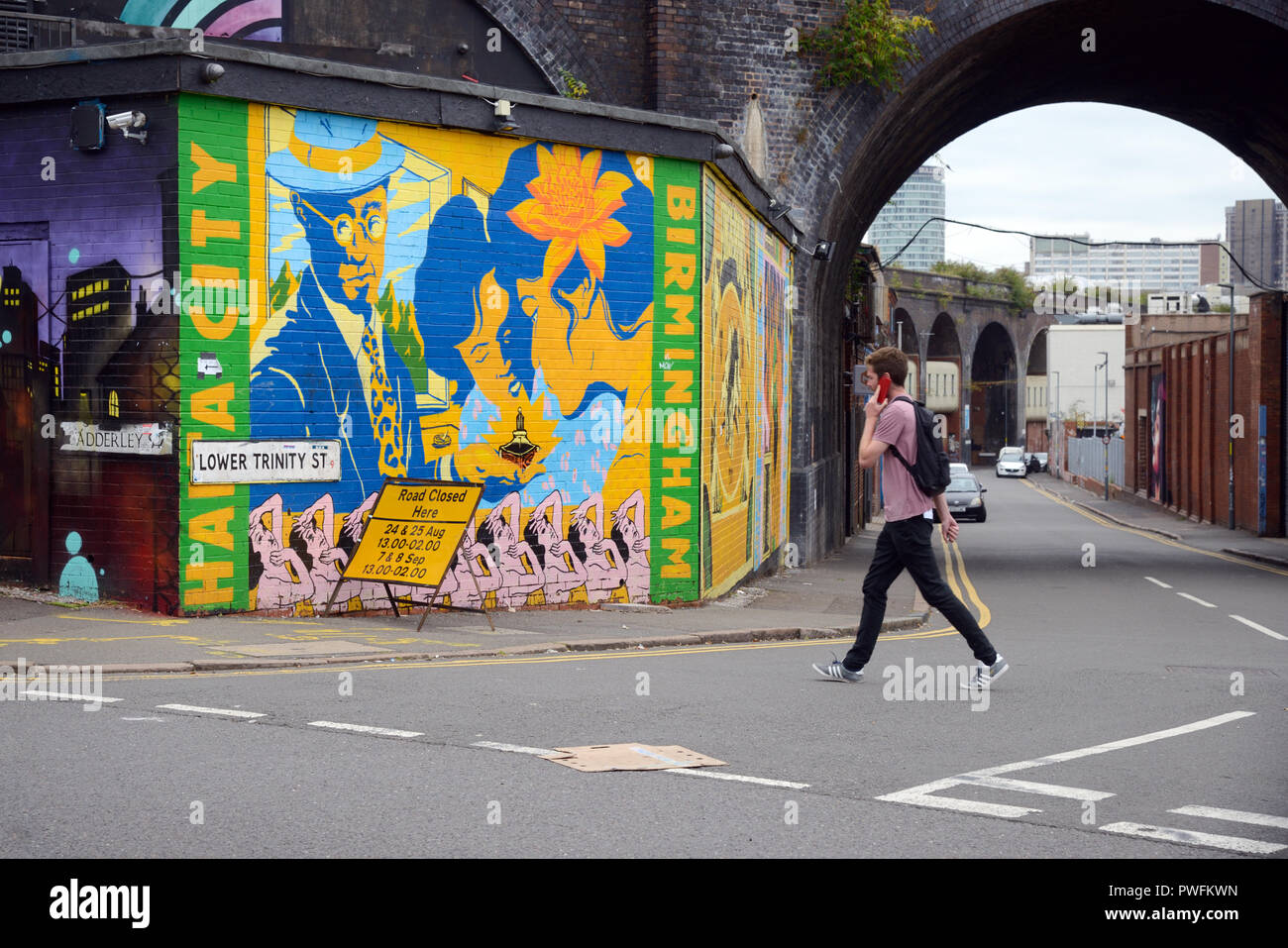 Young Man Walks Past Street Art in the Old Run-Down Streets of Digbeth Birmingham England - Stock Image