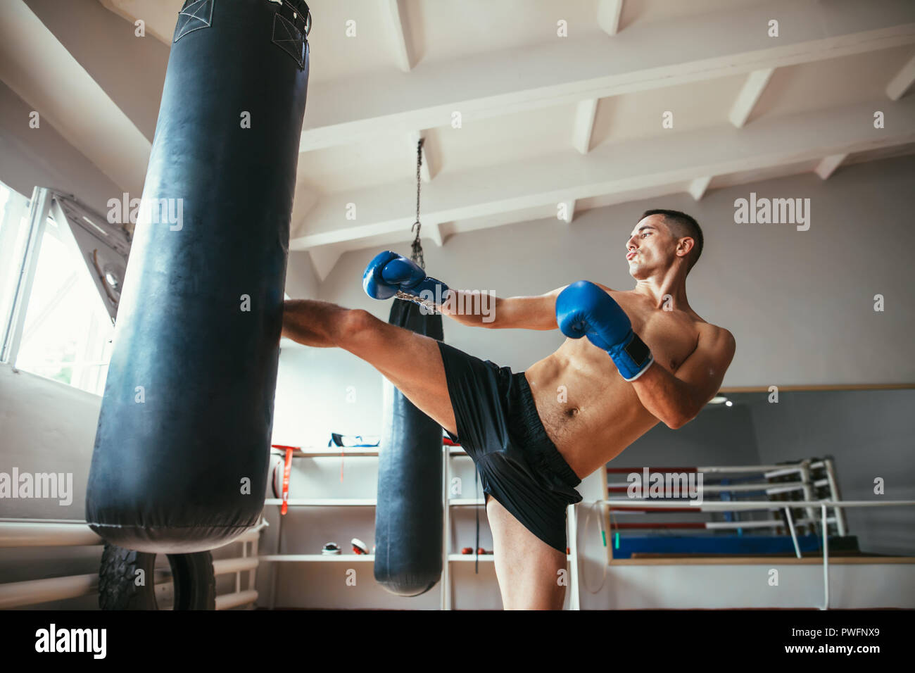 Male boxer workout high kick on the punching bag in gym. Sport concept - Stock Image