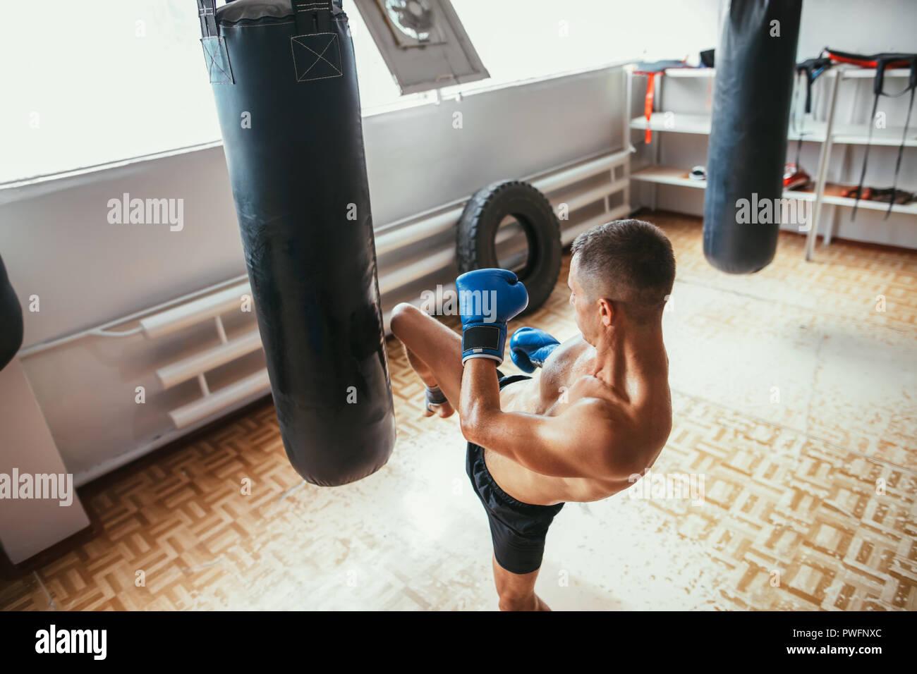 Male boxer hitting punching bag at gym. Boxing, workout - Stock Image