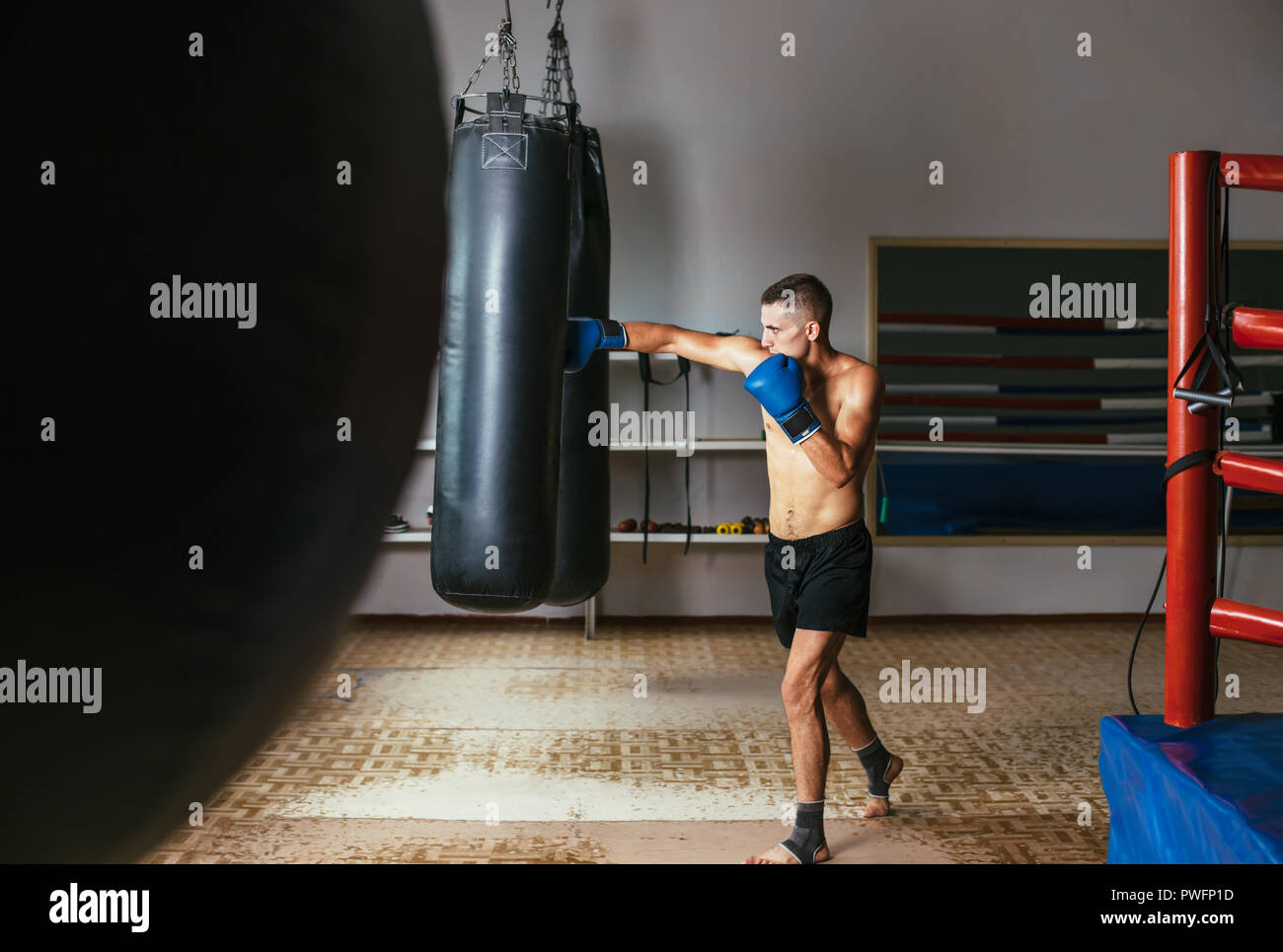 Male boxer hitting punching bag at a boxing studio. Sport training concept - Stock Image