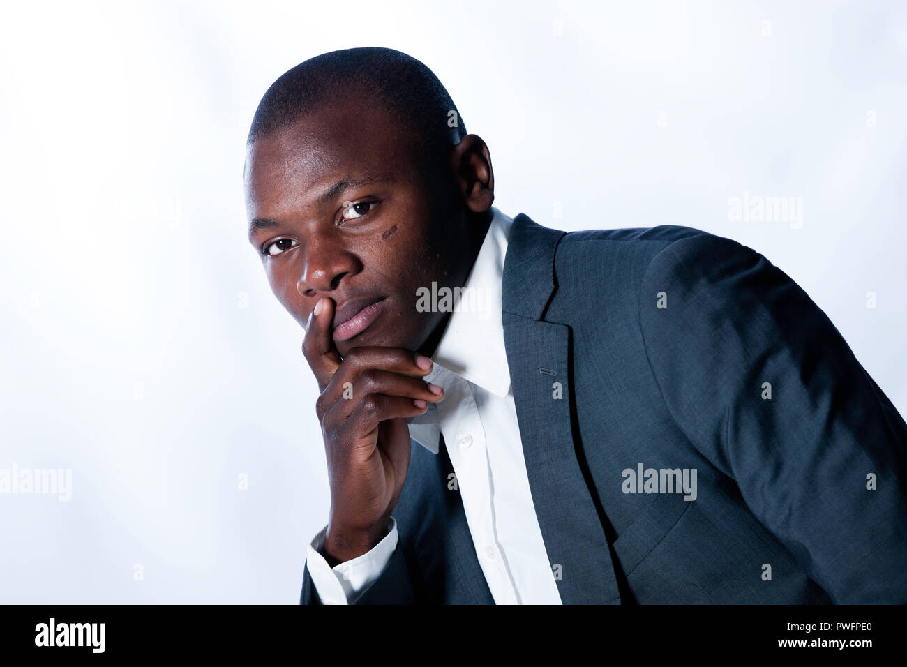 Handsome young african male wearing a business suite looking thoughtfully at the camera with his hand at his chin. White background - Stock Image