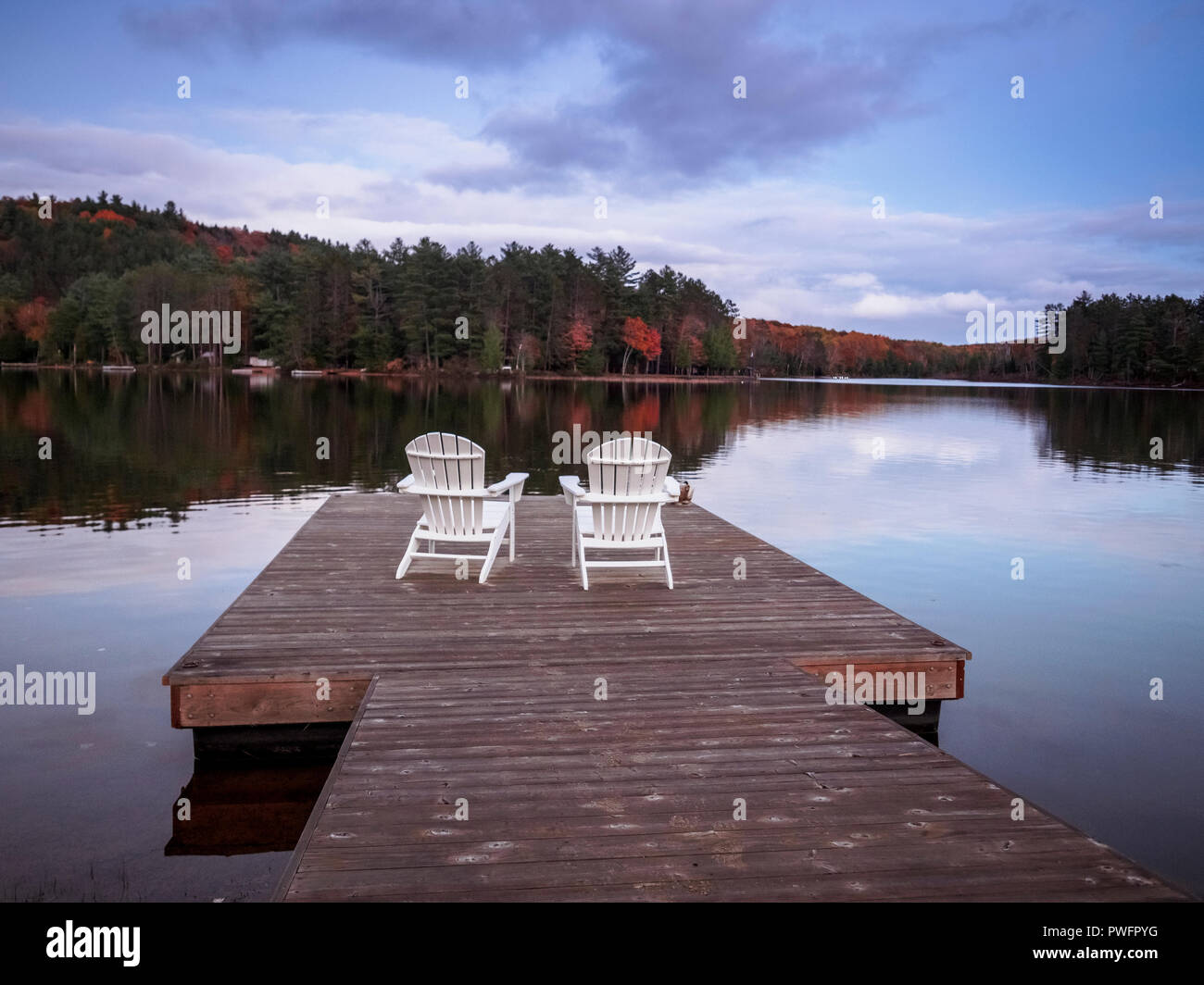 Two Muskoka Chairs in front of lake Benoir, Ontario on a wooden dock. The calm lake water produces stunning reflections. - Stock Image