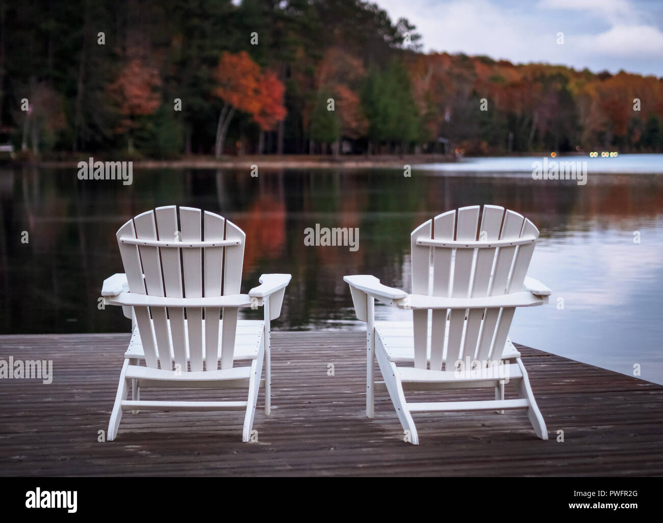 Two Muskoka Chairs in front of lake Benoir, Ontario on a wooden dock during autumn. - Stock Image