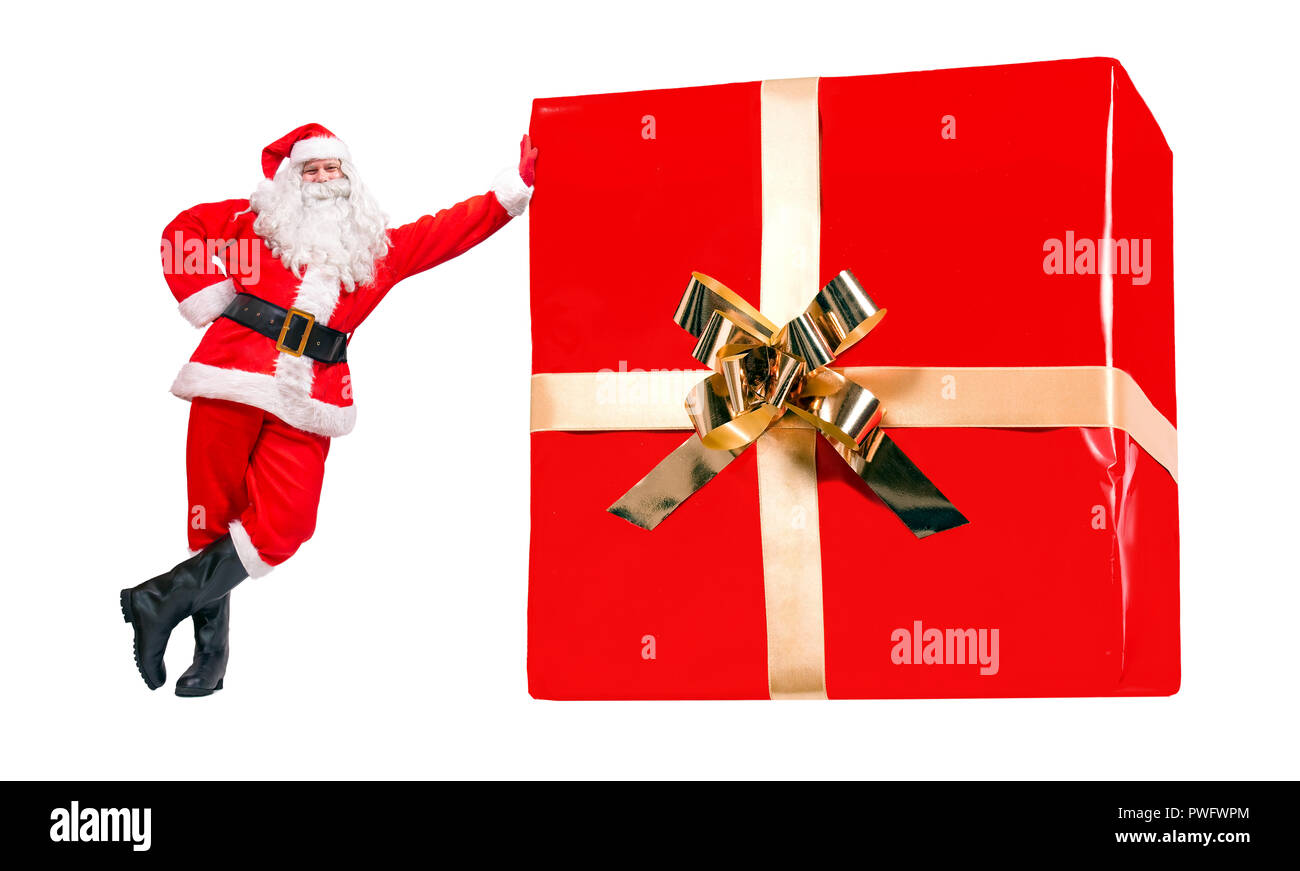 cheerful santa claus stands by the large christmas gift box