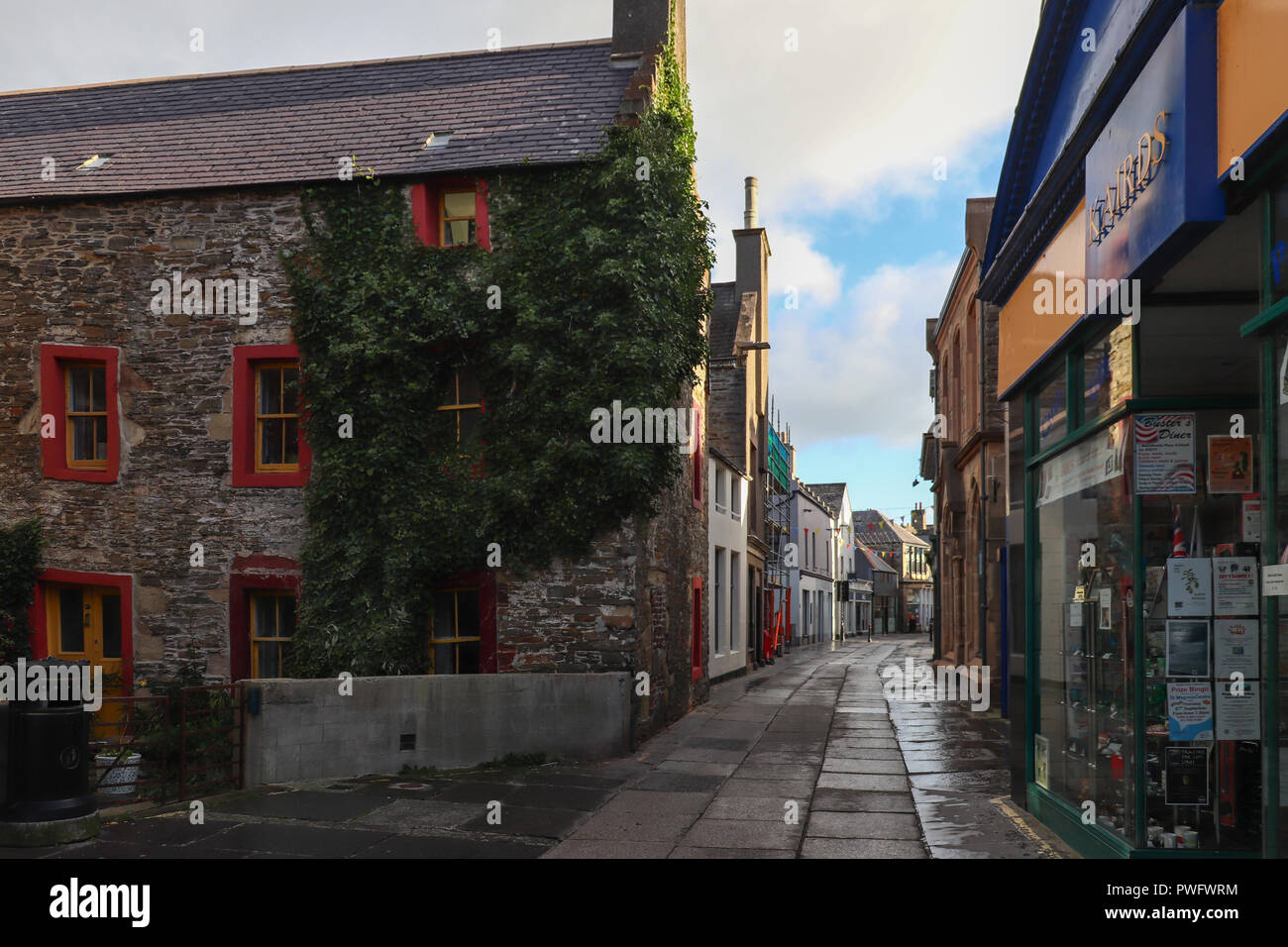 Early Sunday morning on Albert Street in Kirkwall, Orkney, Scotland, with the sun just peeking over the buildings; colorful blue sky, golden light. - Stock Image