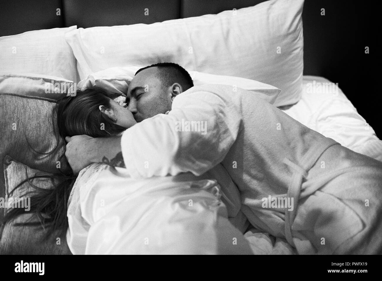 Young romantic couple relaxing and kissing in bed pretty girl and brunette man black and white photo