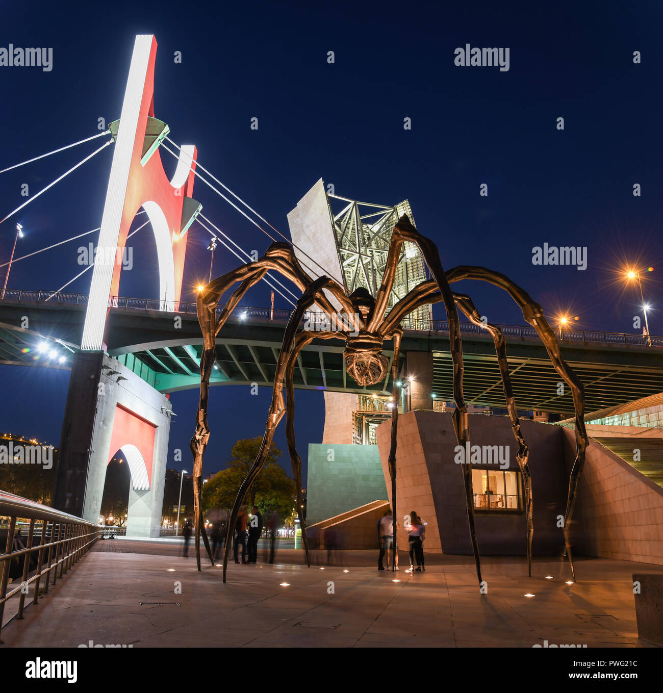 Modern art in Bilbao: spider and reflections at nightfall - Stock Image