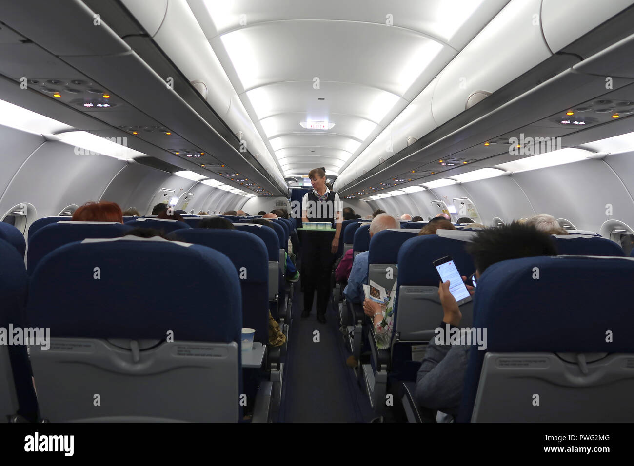 Air attendant serving passengers during a flight of National Air Company Uzbekistan Airways in Uzbekistan - Stock Image