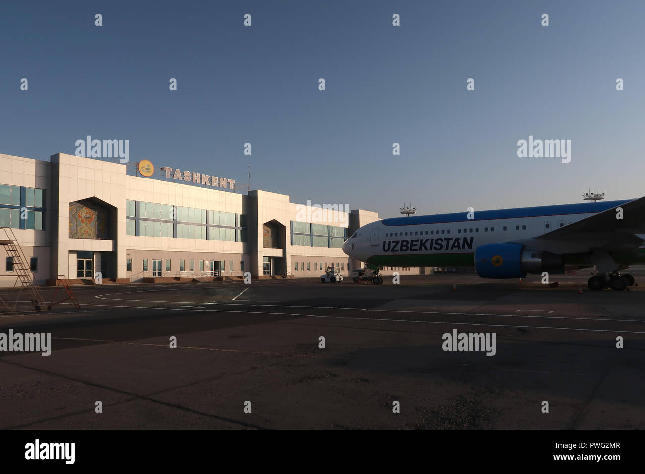 An airplane of National Air Company Uzbekistan Airways stand on the tarmac of terminal 3 for domestic flights in Tashkent Airport, Uzbekistan - Stock Image
