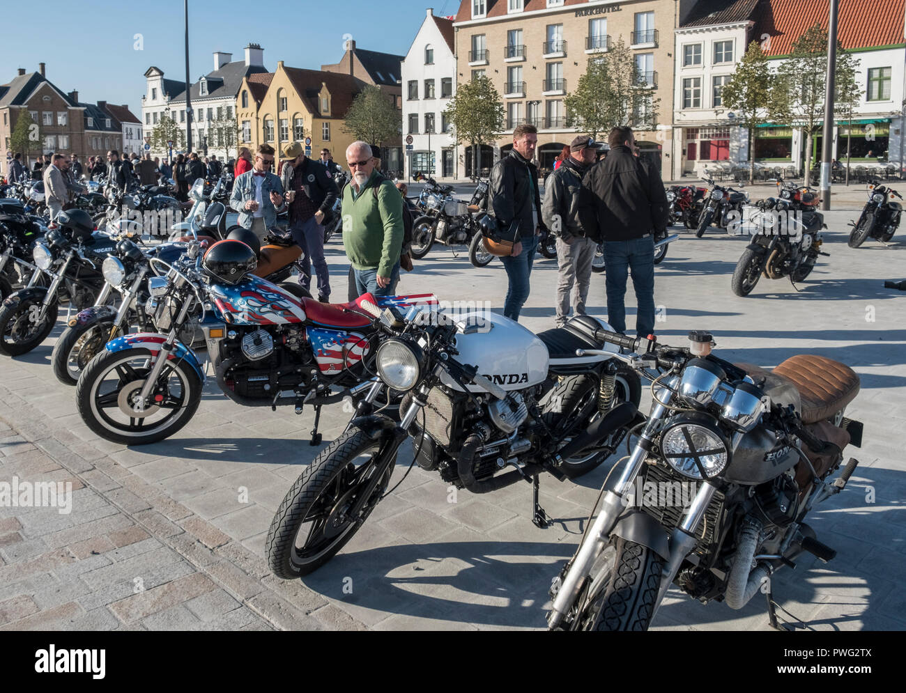 Motorcycle enthusiasts gather on Het Zand Square to admire bikes on display, Bruges, Flanders, Belgium - Stock Image