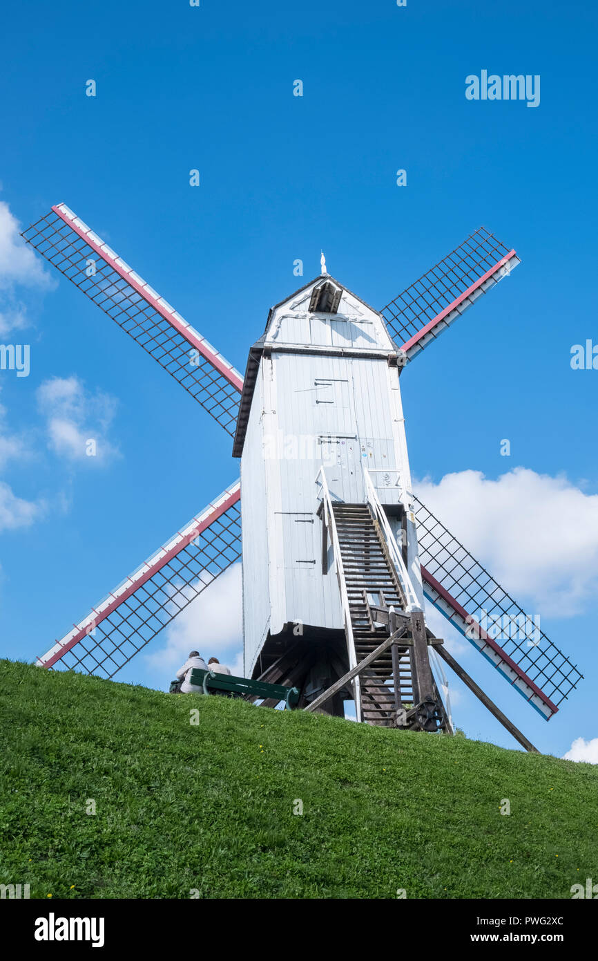 Two people sitting underneath wooden windmill Bonne Chiere, Bruges, West Flanders, Belgium - Stock Image