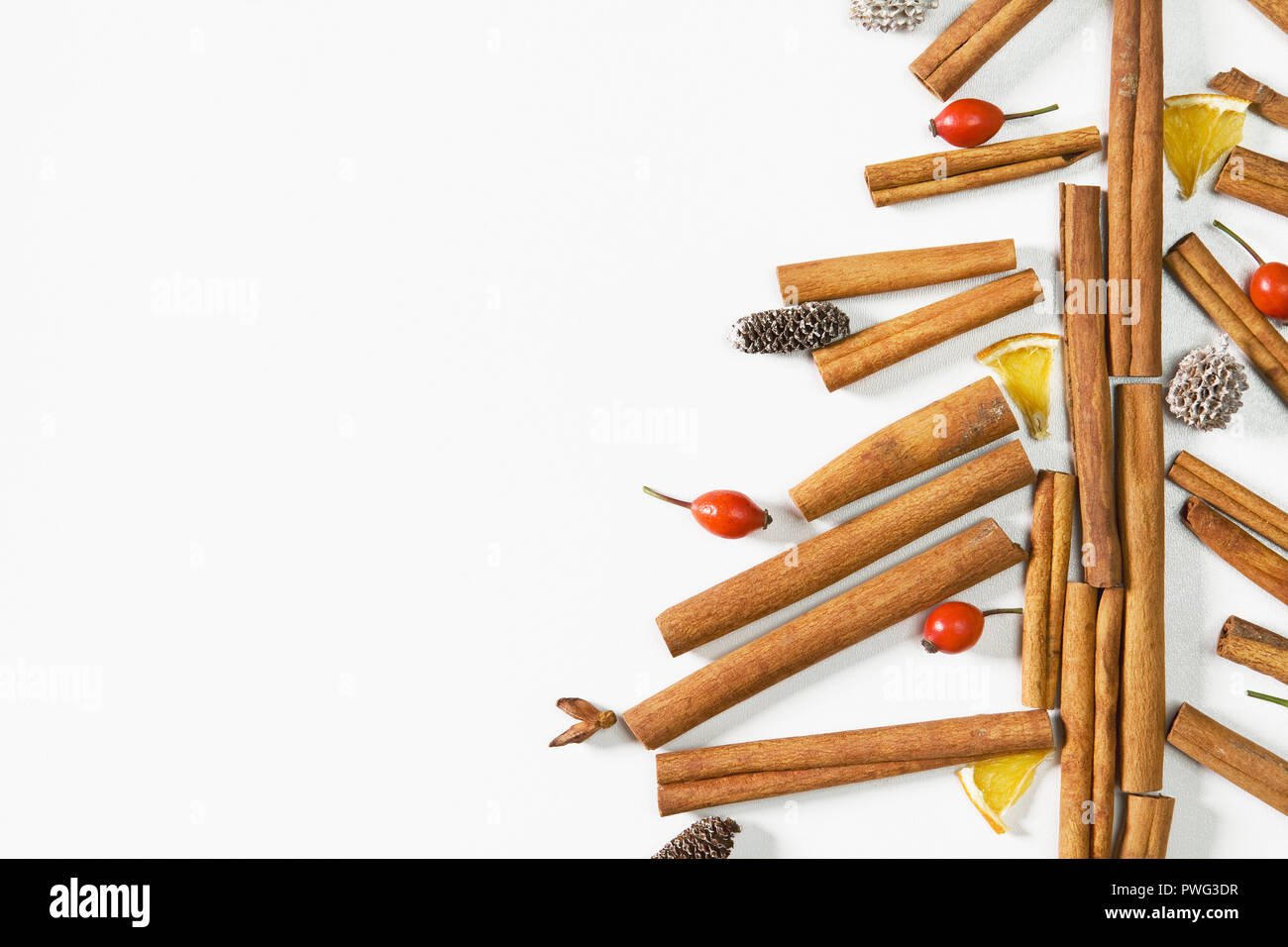Christmas tree made of cinnamon sticks, cones, oranges and rosehip fruits. White background, flat lay, top view. - Stock Image