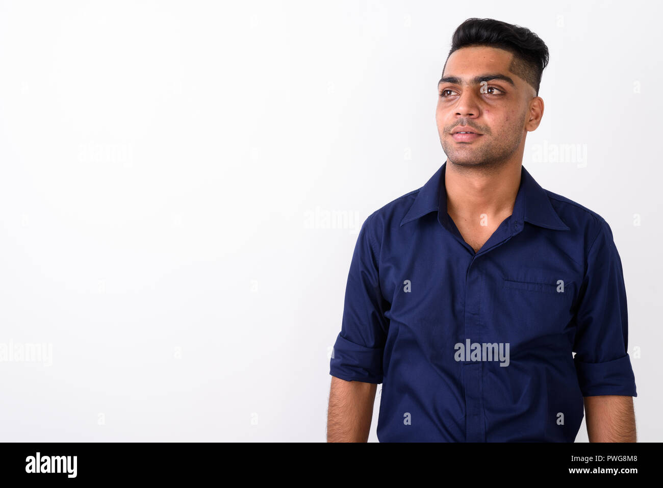 Studio shot of young Indian businessman against white background - Stock Image