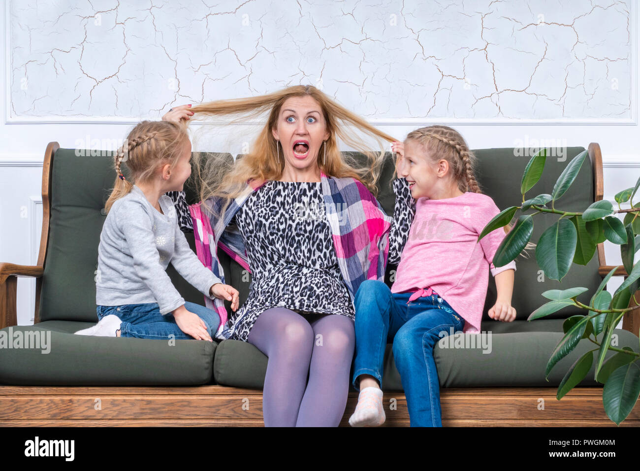 Mother grimacing showing tongue and pulling yourself by the hair amusing their daughters - Stock Image