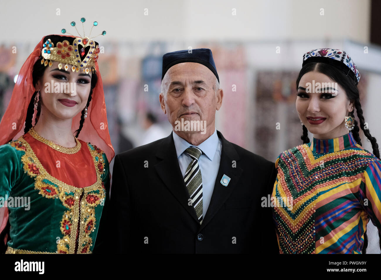 An elderly Uzbek man posing with young women wearing traditional garment in  the city of Tashkent a01aa5fa7e7a
