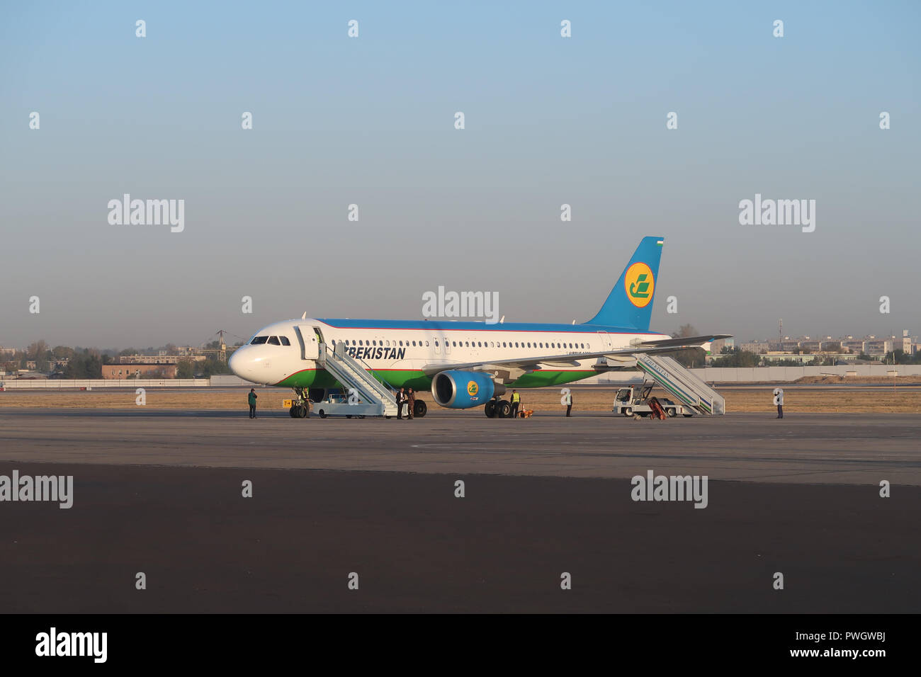 An airplane of National Air Company Uzbekistan Airways stand on the tarmac at Tashkent Airport Uzbekistan - Stock Image