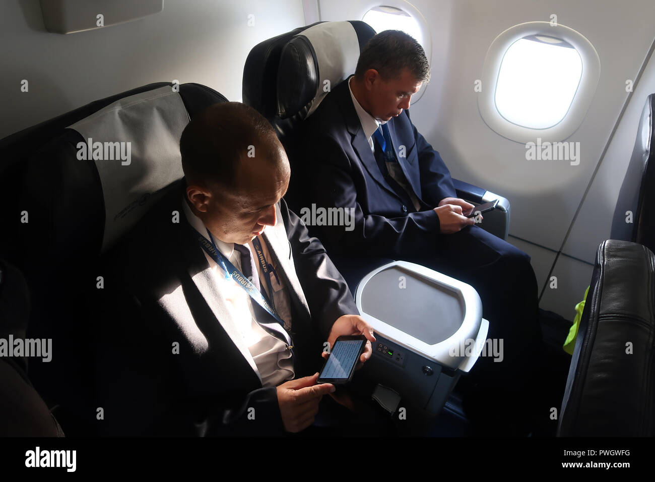 Passengers using their smart phones inside an airplane of National Air Company Uzbekistan Airways - Stock Image