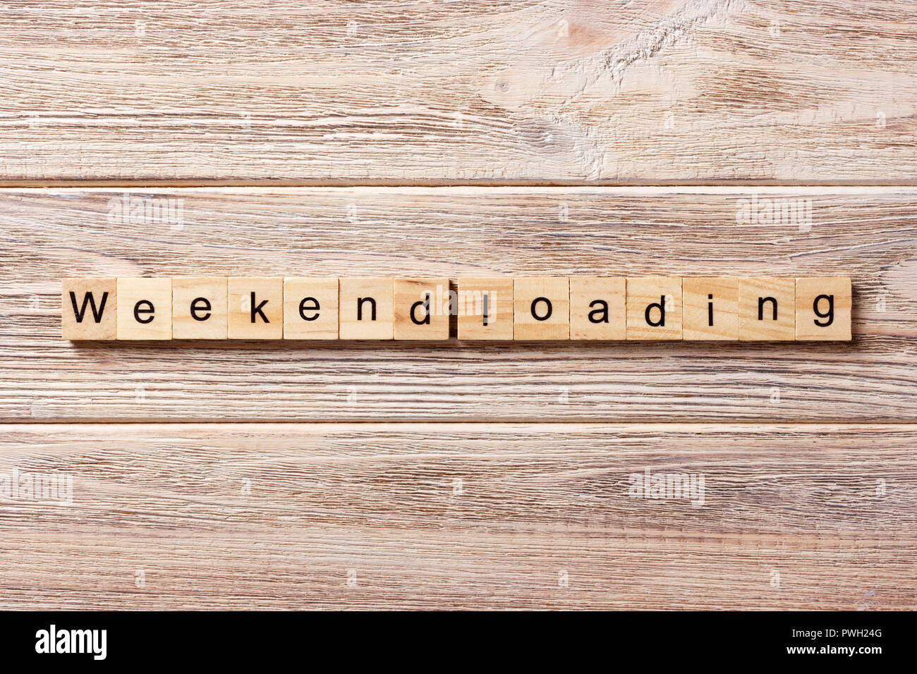 Weekend Loading word written on wood block. Weekend Loading text on table, concept. - Stock Image