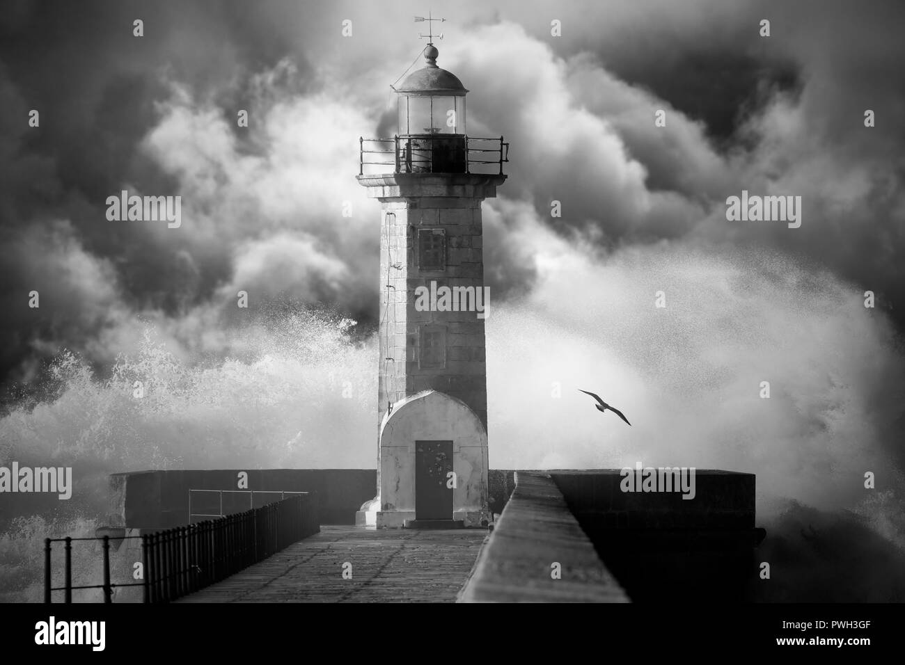 Old lighthouse against an enhanced cloudy stormy sky. Converted black and white. Added digital noise. - Stock Image