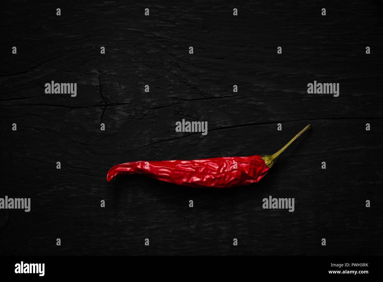 Getrocknete rote Chilischote auf dunklen Untergrund als flatlay - Stock Image