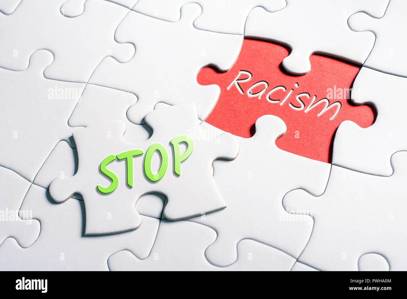 The Words Stop And Racism In Missing Piece Jigsaw Puzzle - Stock Image
