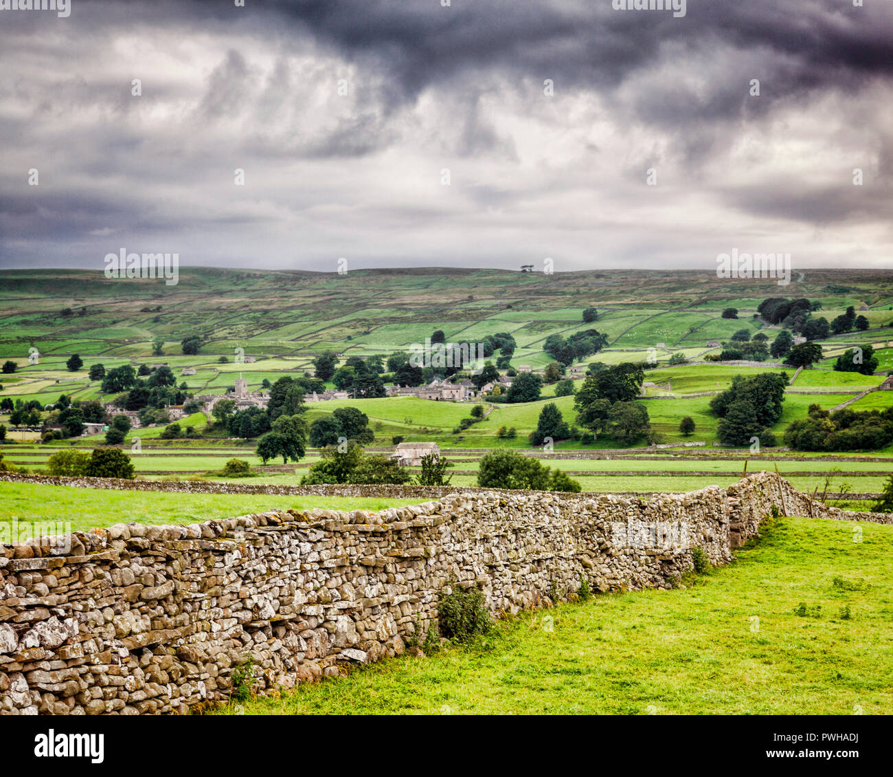 Wensleydale and the village of Askrigg, Yorkshire Dales, England, on an overcast day with a dry stone wall in the foreground. Stock Photo
