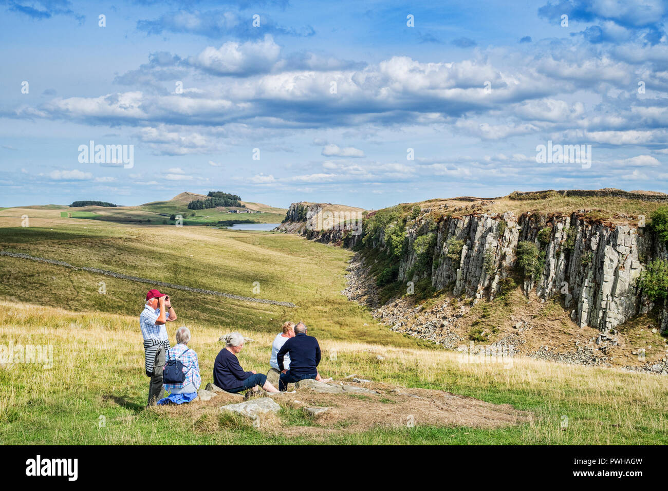 11 August 2018:  Hadrian's Wall, Northumberland, UK - Group of gray haired seniors sitting on the grass at Walltown Crags. - Stock Image