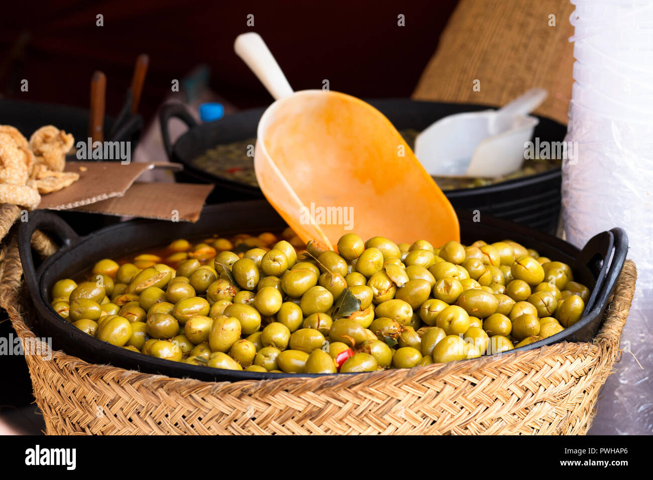 green spanish olives in a basket at street market with a big spoon - Stock Image