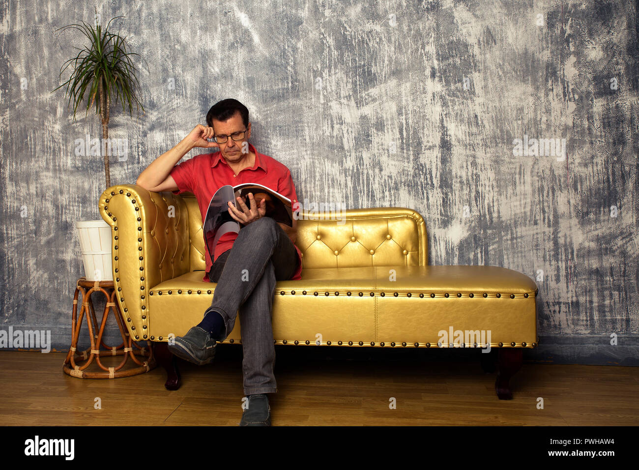 mature man sits on golden leather sofa reading a magazine - Stock Image