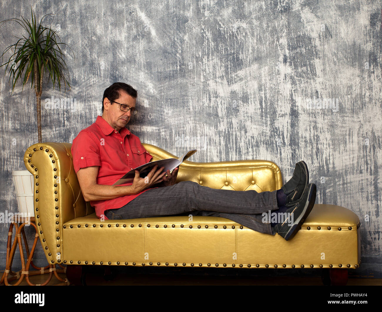 view o man rested on leather sofa reading a magazine - Stock Image