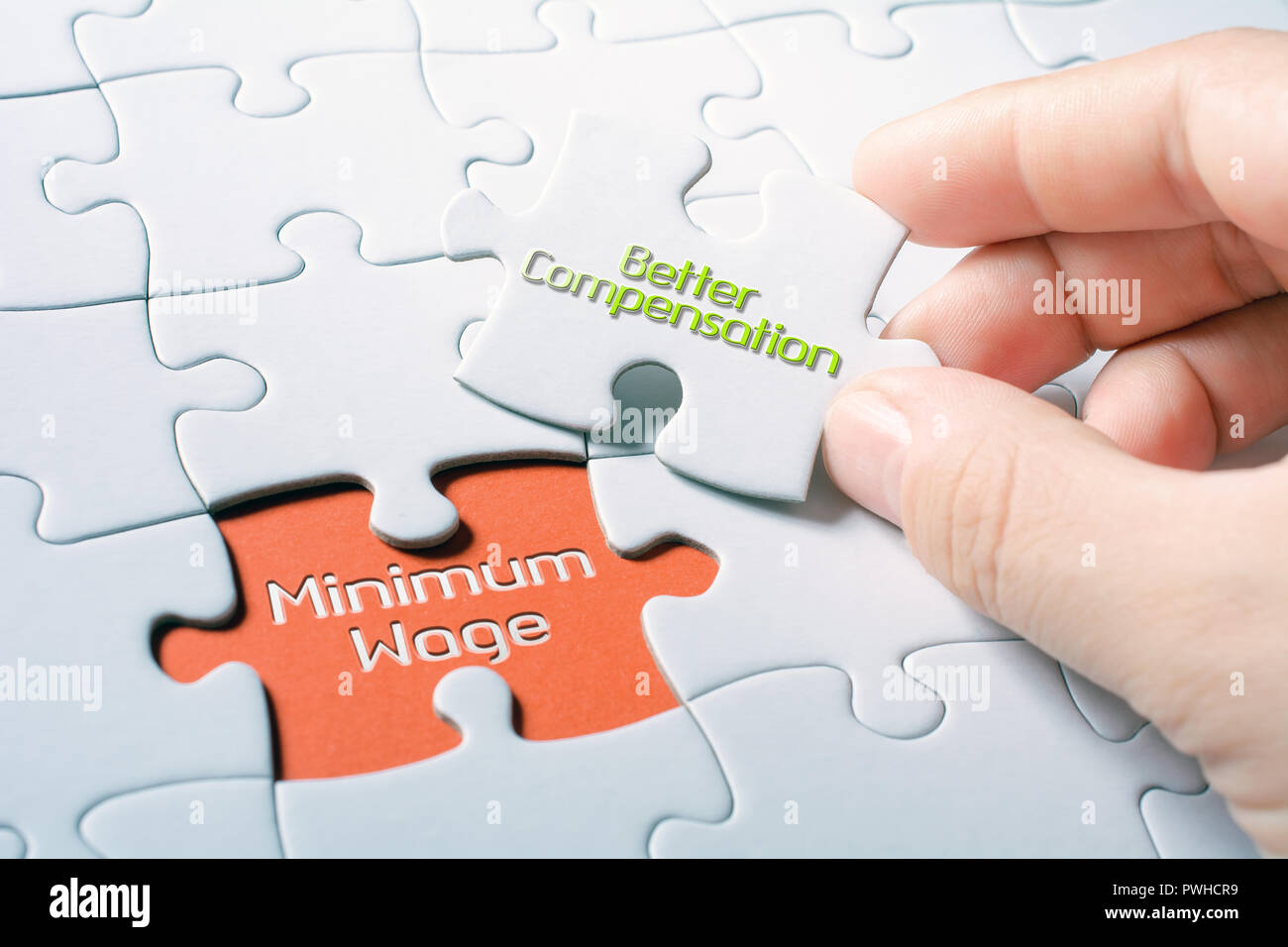 The Words Minimum Wage And Better Compensation In Missing Piece Jigsaw Puzzle - Stock Image