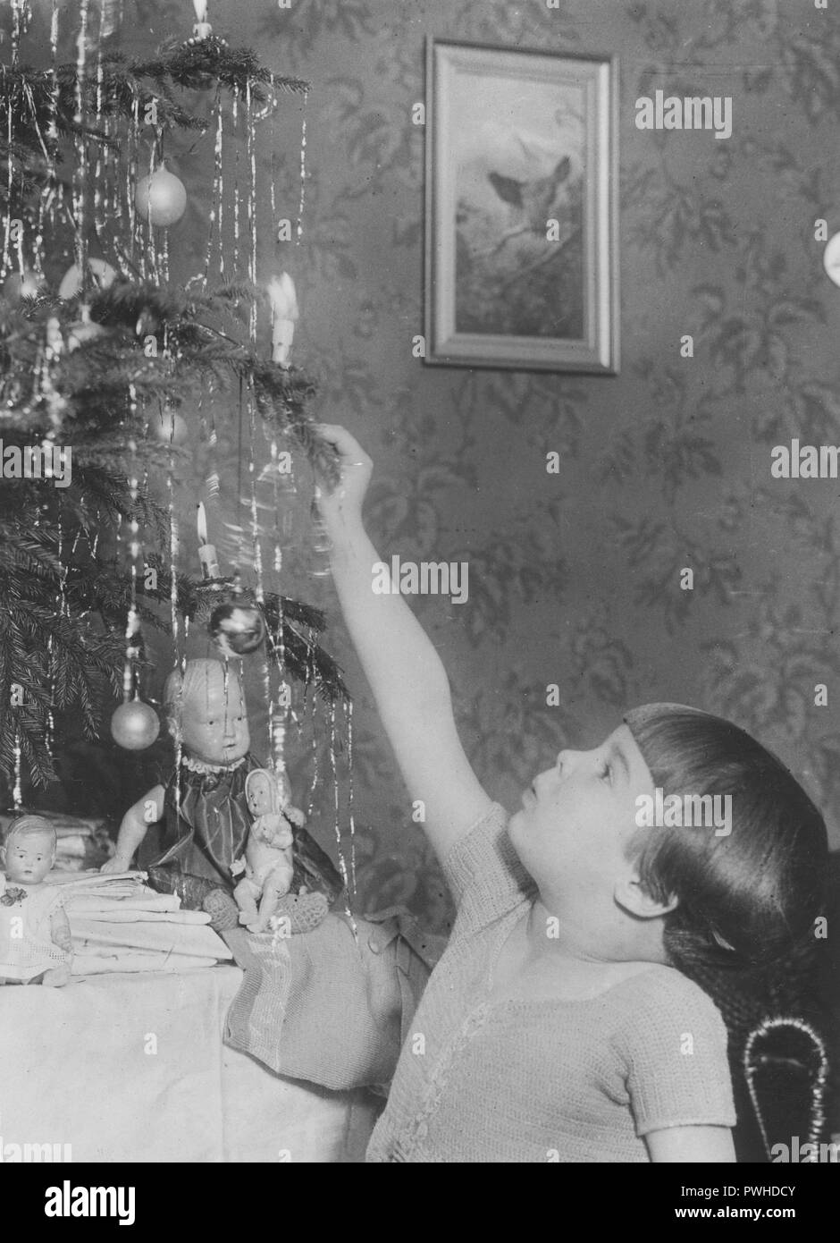 Christmas in the 1920s. A girl is decorating the christmas tree and is lighting a candle in the tree. Sweden 1920s - Stock Image