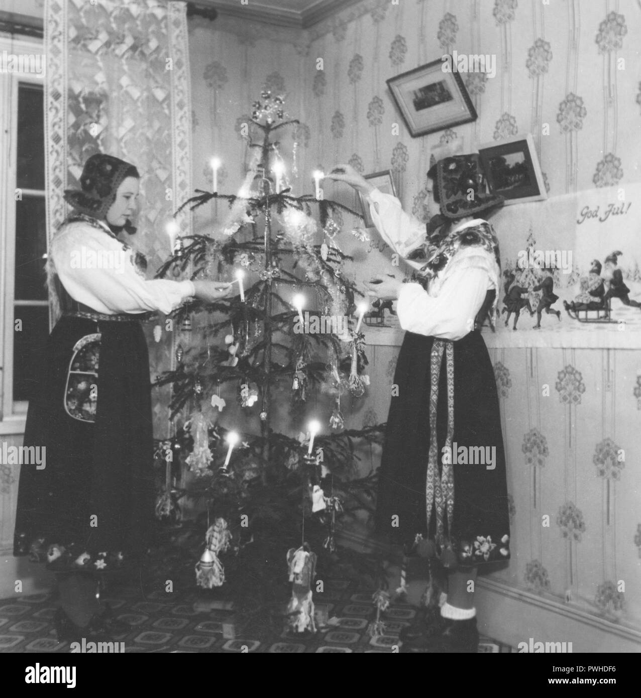 Christmas in the 1940s. Two young women in traditional swedish costumes are lighting the candles in the christmas tree. Dalarna Sweden 1940s - Stock Image