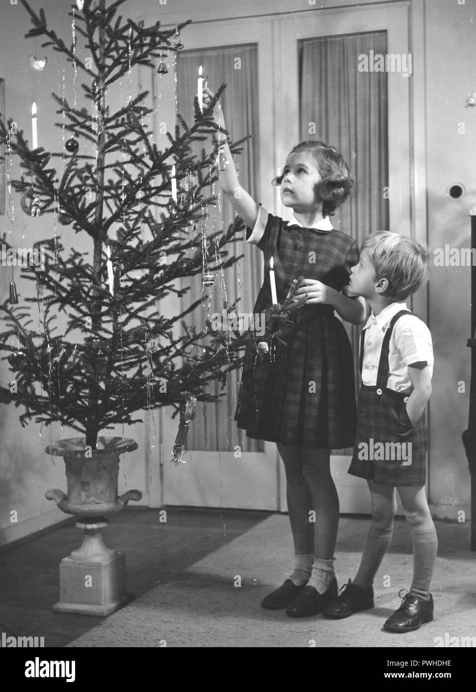 Christmas in the 1950s. A girl and a boy is lighting the candles in the christmas tree. They are nicely dressed for christmas. Sweden 1952 - Stock Image